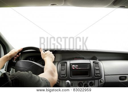 Man's hands of a driver on steering wheel of a minivan car