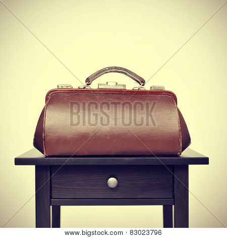 an old doctors bag on a table, with a retro filter effect