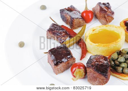 european food: roast beef meat goulash over round white plate isolated over white background with red hot pepper, capers and sauces