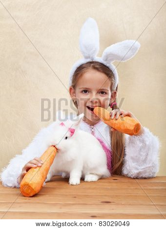 Bunnies eating large carrots - little girl with bunny ears feeding her white rabbit - shallow depth of field