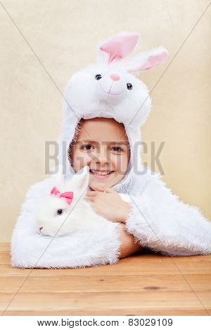 Cute little girl in bunny costume holding her white rabbit - laughing with joy