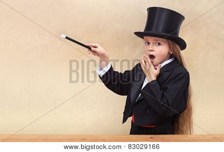 Surprised magician girl with magic wand - copy space on golden background- shallow depth of field