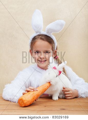 Cute bunnies together - little girl feeding her white rabbit