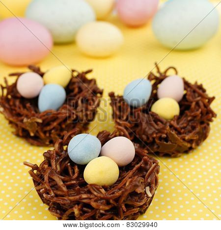 Springtime chocolate nests on yellow background