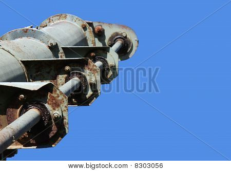 Top gears of a grain auger against a blue sky.