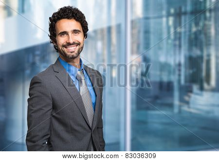 Portrait of a smiling businessman in front of a blue modern background