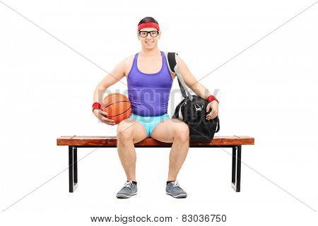 Nerdy athlete holding a basketball seated on a bench isolated on white background