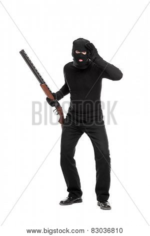 Full length portrait of a burglar with rifle looking through an imaginary glass isolated on white background