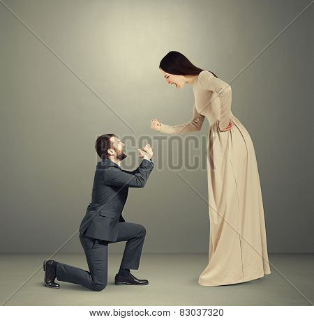 full length portrait of emotional couple over grey background. woman screaming and showing fist, man standing on knee and apologizing