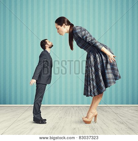 big woman kissing small man. couple in empty room with blue wall