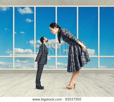 big woman bending forward and kissing small man. photo in room with big windows