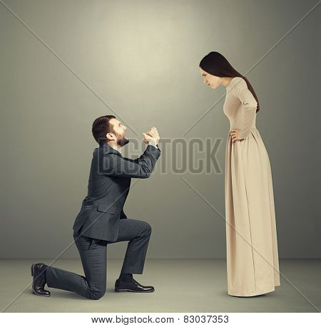 full length portrait of emotional couple over grey background. angry woman looking at man, man standing on knee and apologizing