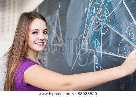 Portrait of a pretty young college student writing on the blackboard during a maths class (color toned image)