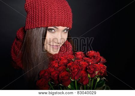 Beautiful Woman with Fresh Red Roses. Girl and Flowers over Black Background. Beauty Female Face. Happiness, Freshness, Beauty, Youth.