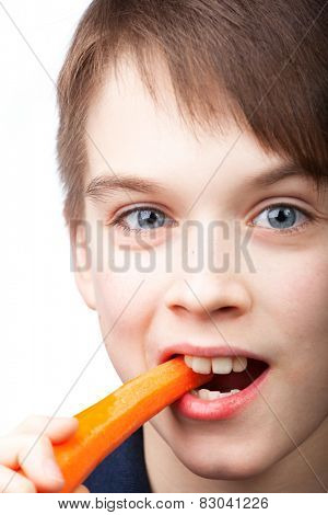 Cute boy bites fresh carrot