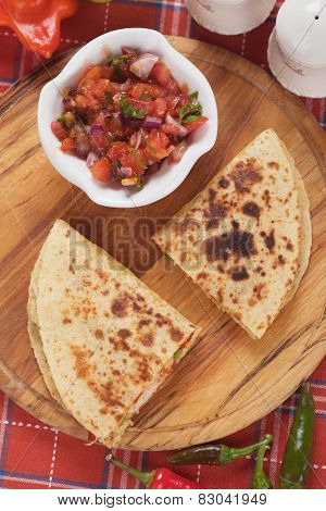 Mexican quesadillas, cheese and vegetable stuffed tortilla with salsa dip