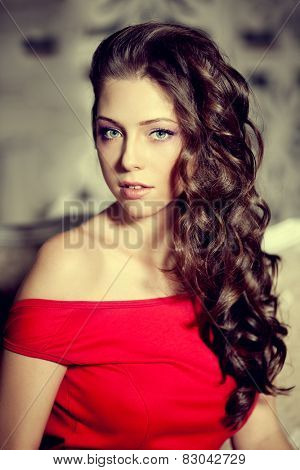 Slim trendy, luxurious, fashion woman in  lux vintage interior with long beauty hairstyle. Girl in red short dress on a luxury background