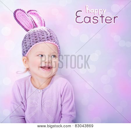 Portrait of cute cheerful Easter bunny, little baby girl wearing pink rabbit ears isolated on blur background with text space, happy spring holidays celebration
