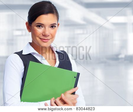 Young businesswoman with folder over office background.