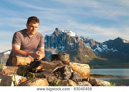 Man And Campfire At Sunset. Tourist Looking To Fire, Kettle