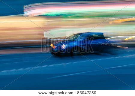 Blue Sports Car In A Blurred City Scene