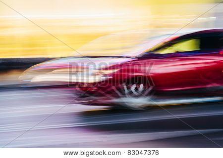 Red Sports Car In A Blurred City Scene