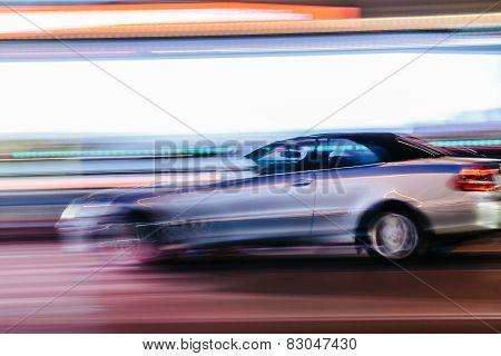 Grey Luxury Car In A Blurred City Scene
