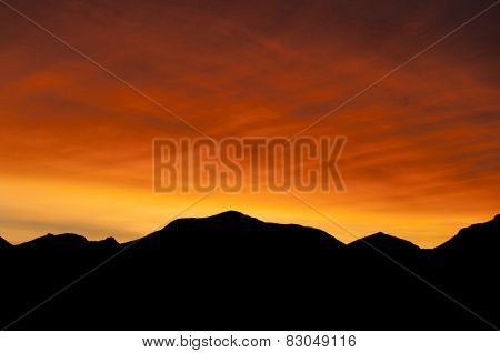 Flaming red sunrise with mountain silhouette