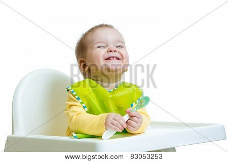 funny baby child sitting in highchair with a spoon