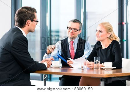 Business - young man in an Job interview, signs his employment contract with boss and his female assistant in their office