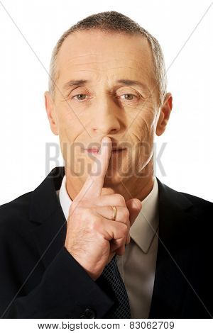 Portrait of businessman gesturing silent sign.