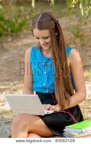 Teen girl works with the laptop in headphones and books