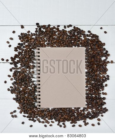 Coffee beans on a white wood table surrounding a blank spiral bound notebook. Shot from a high angle with blank space for copy.