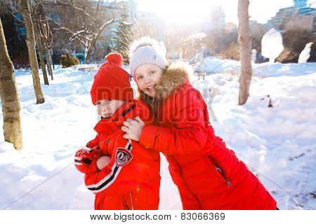 Happy children play down in the snow