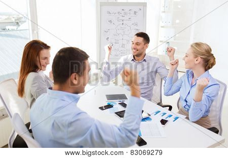 business, people, success and technology concept - smiling business team with tablet pc computers, papers and smartphones showing triumph gesture in office