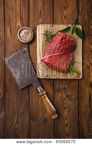 raw beef meat fillet  on wooden  table with meat cleaver and 1lb iron weight