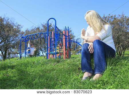 A mother look at boyfriend and children play on the playground