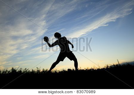 A football player play in back lit day time
