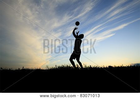A volleyball player play in back lit day time