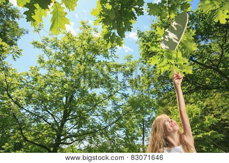 A little girl try to catch heart on a tree