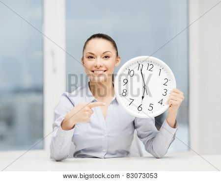business, office, school and education concept - attractive businesswoman pointing finger to clock