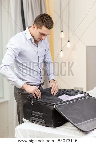 business, technology, internet and hotel concept - happy businessman packing things in suitcase in hotel room