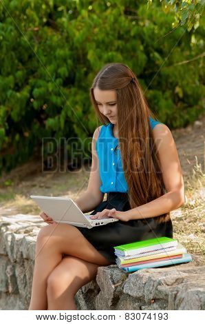 Teen girl works with the laptop and books