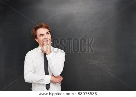 Smiling young man on chalkboard background