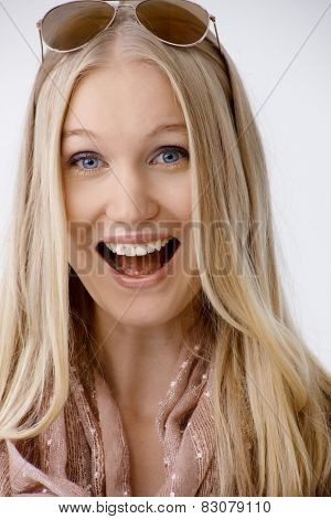 Attractive blonde woman shouting, laughing happy, looking at camera.