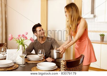 Young couple having dinner at home, waiting for friends.
