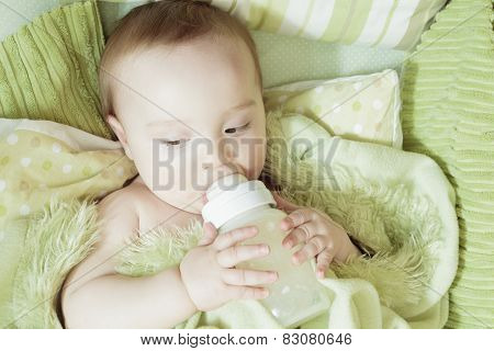 Funny little baby with beautiful standing in a round white crib