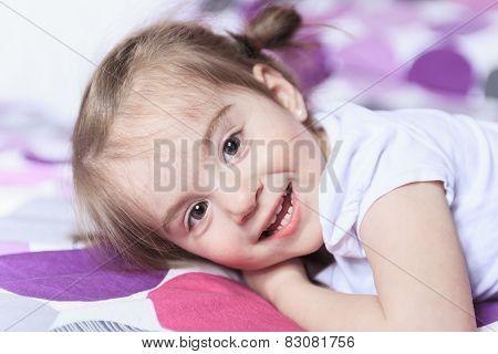 Little girl lying on bed in room