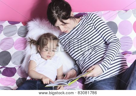 Mother and young daughter reading book in the bed room