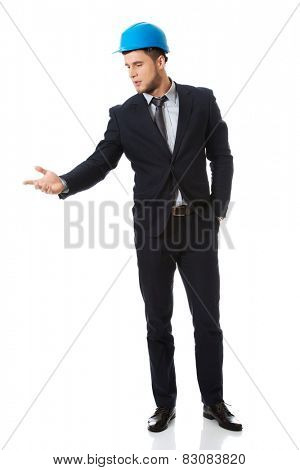 Happy businessman with blue hard hat holding copy space.